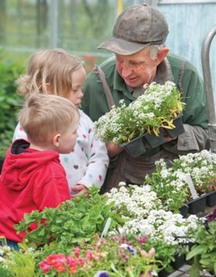 Gardener showing flowers to 2 children